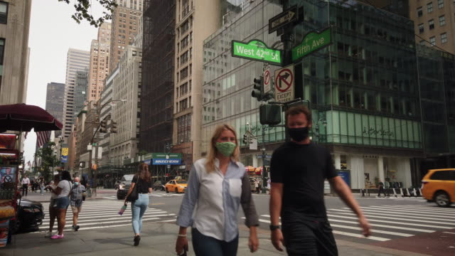 new york city 42nd street and 5th avenue during coronavirus pandemic . people crossing the street and wearing protective face masks and coverings.... - 42nd street stock videos & royalty-free footage