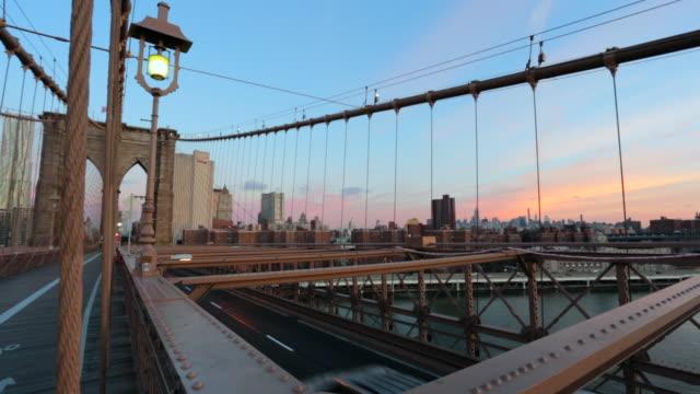 new york city brooklyn bridge bei sonnenaufgang - gelbes taxi stock-videos und b-roll-filmmaterial