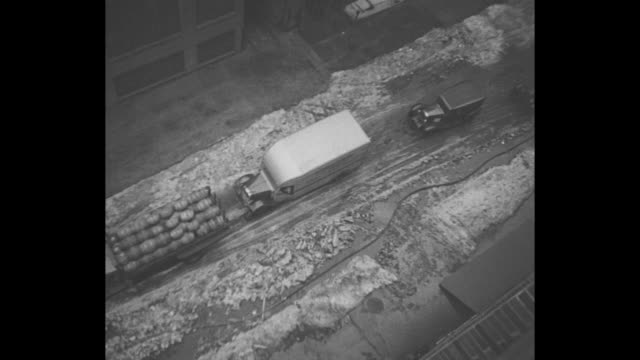 [New York City] Car on slushy street tilt down to its wheels splashing through halfmelted ice / VS firemen and street department workers hack at...