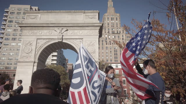 stockvideo's en b-roll-footage met new york city celebrating joe biden winning 2020 election beating donald trump. man and woman standing on the washington square benches waving a... - opluchting