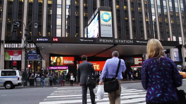 new york city commuters cross the street to enter new york penn station in midtown manhattan madison square garden exteriors - new york city penn station stock videos and b-roll footage