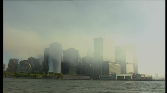 vídeos y material grabado en eventos de stock de new york city coping in the aftermath of 9/11 shows exterior wide shot of island of manhattan with smoke rising from the centre of the buildings on... - caos