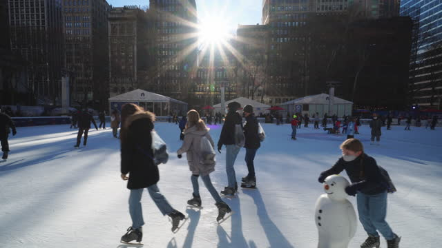 new york city – december 27 2020: people enjoy ice skating at bryant park on sunday afternoon, amidst the covid-19 pandemic during the winter holiday... - bryant park stock videos & royalty-free footage
