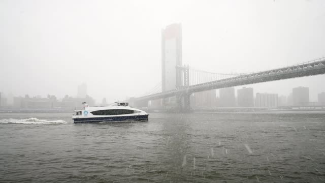 vídeos de stock, filmes e b-roll de a new york city ferry makes its way along the east river during a snowstorm march 21 2018 in new york city the fourth nor'easter of the month hit the... - atlântico central eua