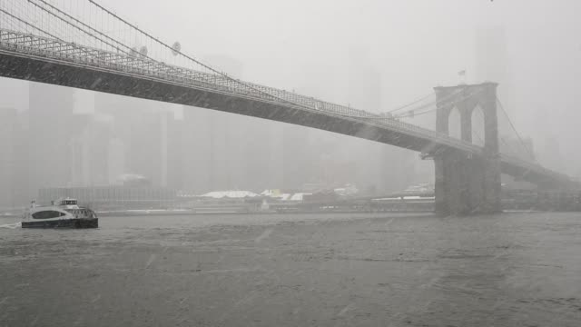 vídeos de stock, filmes e b-roll de a new york city ferry passes under the brooklyn bridge during a snowstorm march 21 2018 in new york city the fourth nor'easter of the month hit the... - atlântico central eua