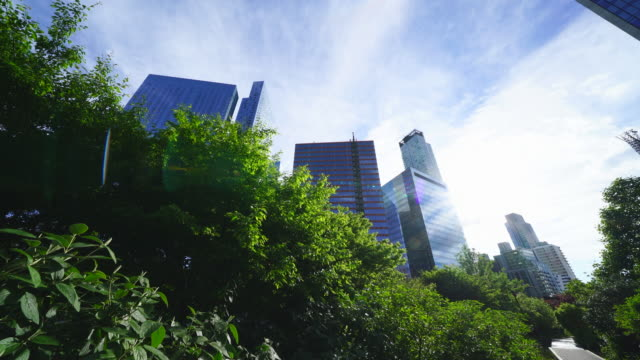 new york city high-rise office buildings stand over the fresh green trees at queens ny usa on may 27 2019. trains run on the elevated railway track beside the big fresh green tree at queens ny usa on may 27 2019. - commuter train stock videos & royalty-free footage