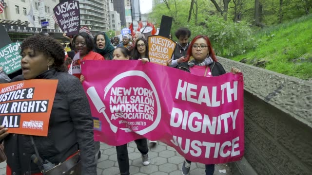 new york city international workers day demonstrators gathered at columbus circle 59th street near the trump international hotel & tower new york in... - 労働組合点の映像素材/bロール
