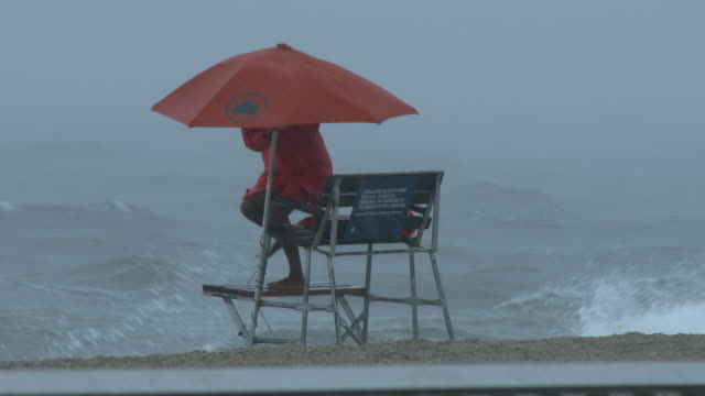 a new york city lifeguard adjusts his umbrella and watches over the beach as rough surf churns along the shoreline in front of him and torrential... - scott mcpartland stock videos & royalty-free footage
