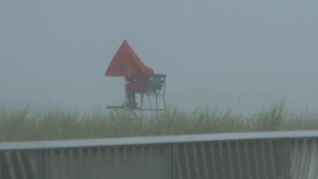 a new york city lifeguard adjusts his umbrella and watches over the beach as rough surf churns along the shoreline in front him and torrential rain... - scott mcpartland stock videos & royalty-free footage