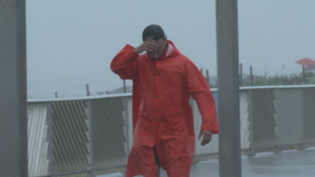 a new york city lifeguard shields his face from wind driven torrential rain during tropical storm fay on rockaway beach queens new york new york - scott mcpartland stock videos & royalty-free footage