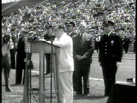 New York City Mayor Fiorello H LaGuardia standing behind podium on unidentified field location w/ people seated in stands bleachers BG SOT saying...