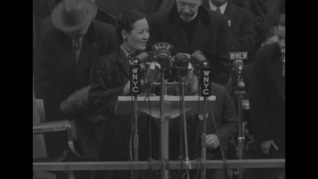 new york city mayor fiorello la guardia stands at microphonelined podium outside ny city hall giving speech as mme chiang kaishek sits on platform... - chiang kai shek stock-videos und b-roll-filmmaterial