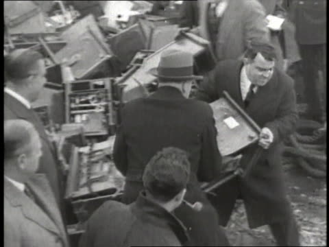 New York City Mayor Fiorello LaGuardia helps throw a slot machine off a barge