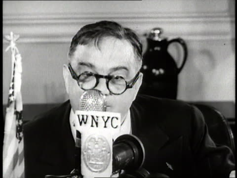 New York City Mayor Fiorello LaGuardia reads a newspaper for a radio broadcast during a newspaper strike