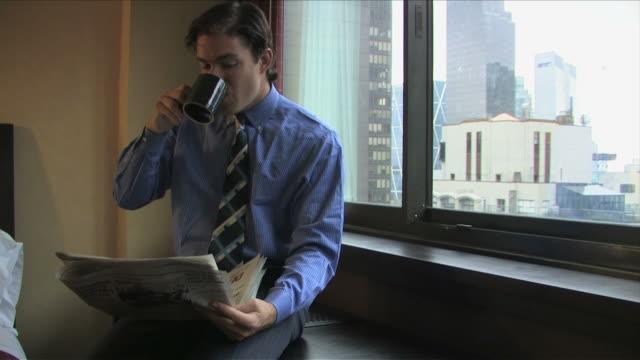 vídeos de stock, filmes e b-roll de new york city, new york, usaone business man is reading the newspaper in the room - só homens jovens