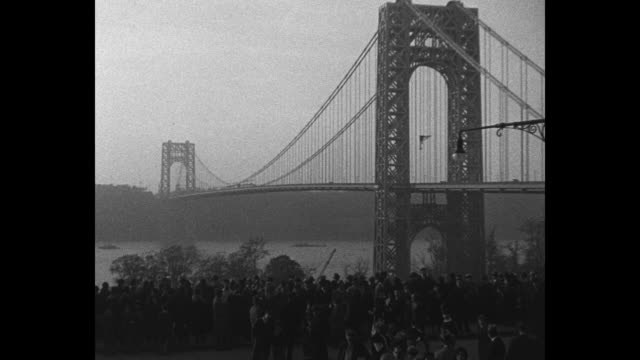 ws crowd stands on shore with george washington bridge stretching across the hudson river / firth of forth scotland boat moves away as it passes... - fluss firth of forth stock-videos und b-roll-filmmaterial