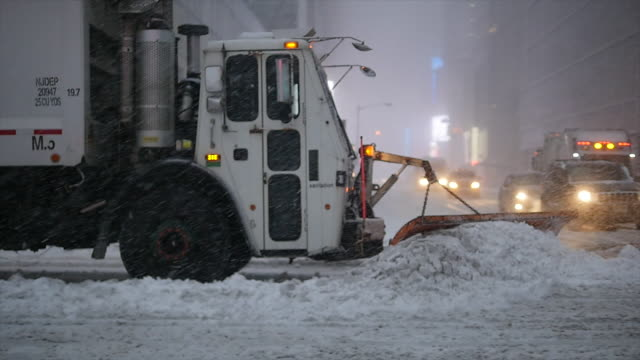 new york city on a snow blizzard storm day. urban streets covered with snow - snowplough stock videos & royalty-free footage