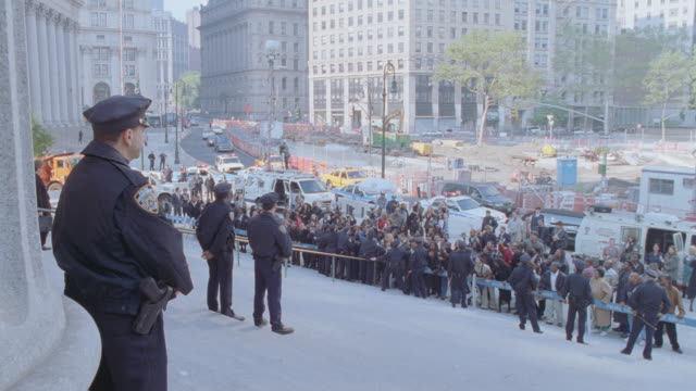 new york city police officers stand on the steps of the courthouse while protesters demonstrate behind the police line. - 抗議者点の映像素材/bロール