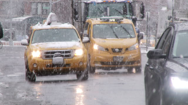 New York City road traffic in a snow storm.   Taxi's and cars navigate slippery wintery streets.