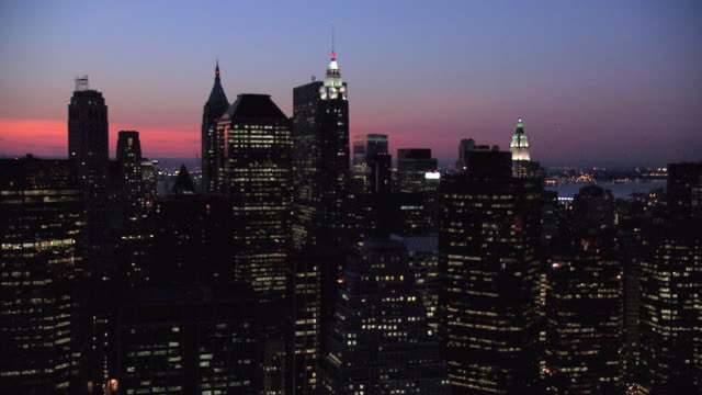 aerial new york city skyline and the woolworth building lit up at sunset / new york, united states - woolworth building stock videos & royalty-free footage