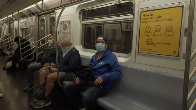 new york city subway during coronavirus pandemic. yellow mta poster showing how to properly wear face masks. people sitting socially distant and... - new york city subway stock videos & royalty-free footage