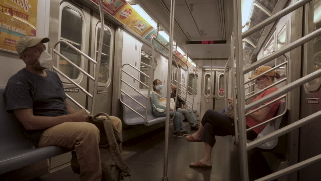 new york city subway interior during coronavirus phase 3. people are wearing masks and practicing social distancing by sitting far apart. - new york city subway stock videos & royalty-free footage