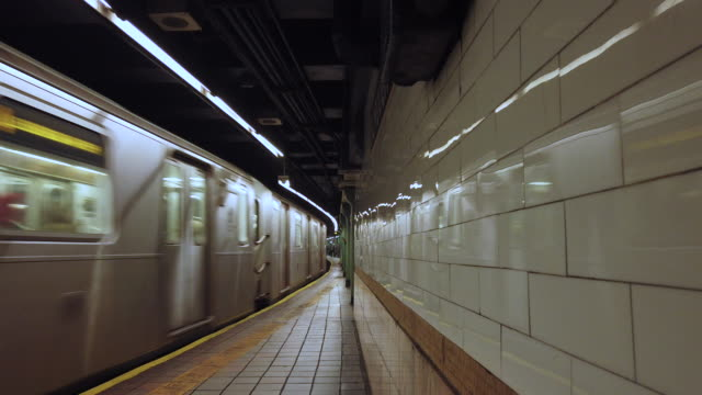 new york city subway train arrives at station - moving past video stock e b–roll