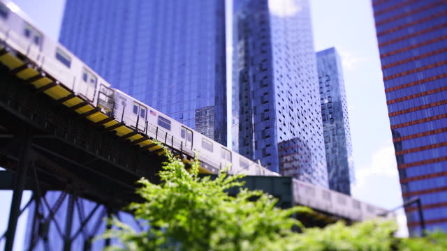 new york city subway trains run on the elevated railway track among the high-rise buildings along the fresh green trees-lined street at queens ny usa on may 27 2019. - elevated train stock videos & royalty-free footage