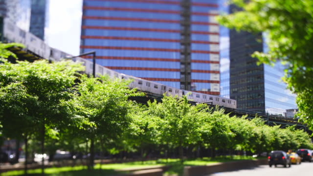 new york city subway trains run on the elevated railway track among the high-rise buildings along the fresh green trees-lined street at queens ny usa on may 27 2019. - queens new york city stock videos & royalty-free footage