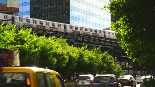 new york city subway trains run on the elevated railway track among the high-rise buildings along the fresh green trees-lined street at queens ny usa on may 27 2019. - hochbahn passagierzug stock-videos und b-roll-filmmaterial