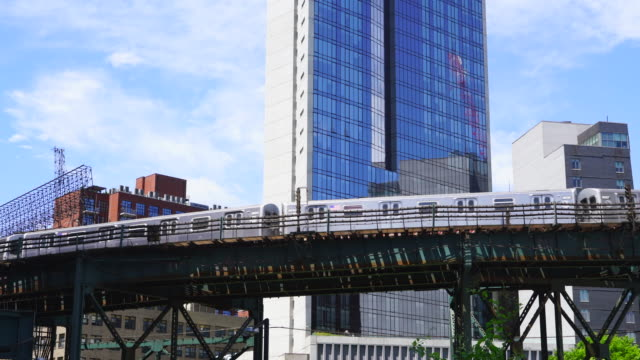 new york city subway trains run on the elevated railway track beside the high-rise buildings at queens ny usa on may 25 2019. - hochbahn passagierzug stock-videos und b-roll-filmmaterial
