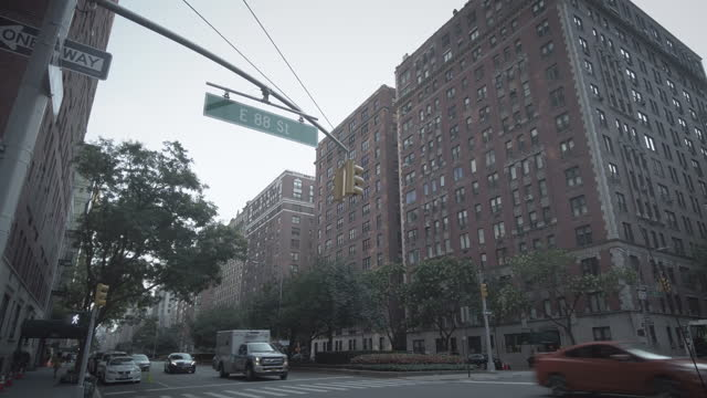 vídeos de stock e filmes b-roll de new york city upper east side neighborhood with buildings, traffic with yellow taxi, ambulance, fire truck and people. filmed on 89th street and park... - yellow taxi