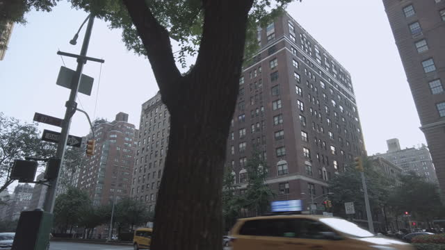new york city upper east side neighborhood with buildings, traffic with yellow taxi, garbage truck and people. - segnale per macchine e pedoni video stock e b–roll