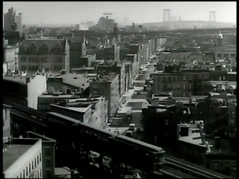 new york city w/ mixed architecture & mixed age buildings elevated subway train moving below fg unidentified bridge in fog bg. - new age stock-videos und b-roll-filmmaterial
