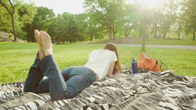 vídeos y material grabado en eventos de stock de la ciudad de nueva york joven mujer descansando en el sol en el parque - manta ropa de cama
