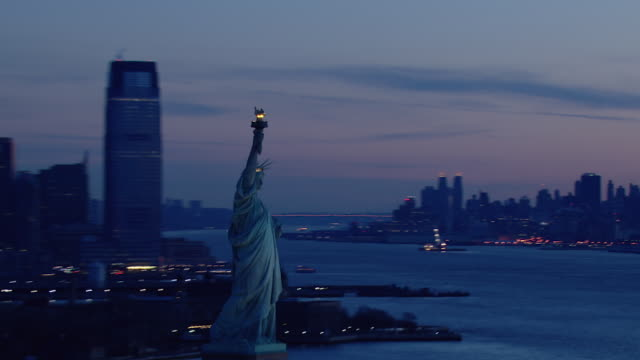 new york city's famous statue of liberty greets the dawn. - ジャージーシティ点の映像素材/bロール
