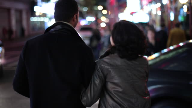vídeos y material grabado en eventos de stock de new york couple cross busy street, stopping to kiss amid the bright lights of times square as cars drive past - guay