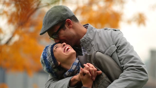 New York couple in love laugh as they hold each other in autumn park (dolly-shot)