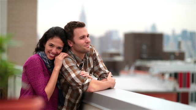 New York couple in love on Brooklyn rooftop, girl smiles at camera as guy looks out over skyline (dolly-shot)