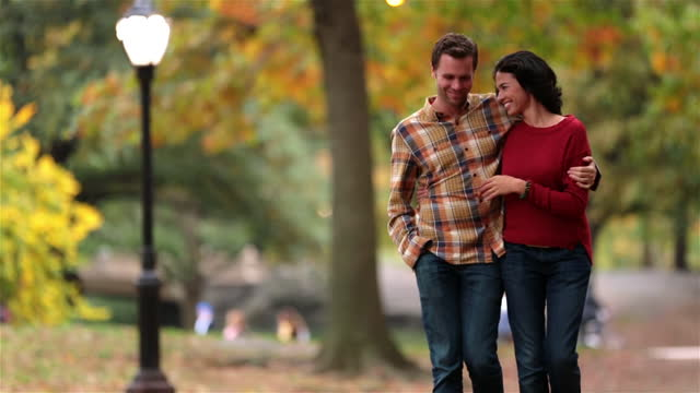 New York couple stroll through Central Park in fall, boy wraps arm around and kisses girlfriend on forehead