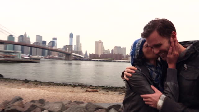 New York couple walk together along the East River toward the Brooklyn Bridge, girl kisses boy