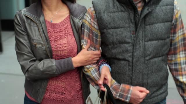 vídeos de stock, filmes e b-roll de new york couple with shopping bags walk arm-in-arm up sidewalk in soho - de braços dados