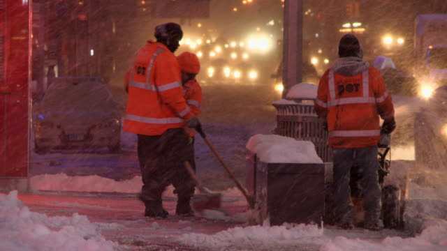 New York DOT officials shovel snow during a heavy snowfall
