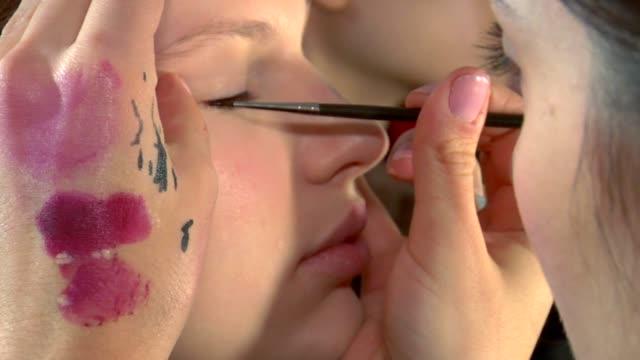 new york fashion week. a model gets makeup applied backstage at the carolina herrera fashion show. at the general coverage: new york fashion week at... - new york fashion week stock videos & royalty-free footage