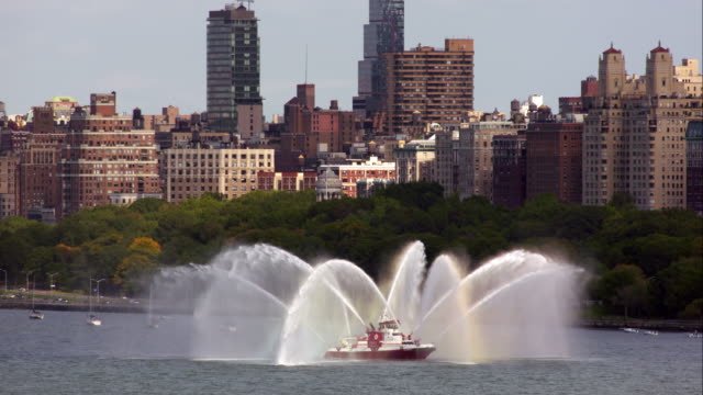 New York Fire Department boat sprays fire hoses into the air on the Hudson River