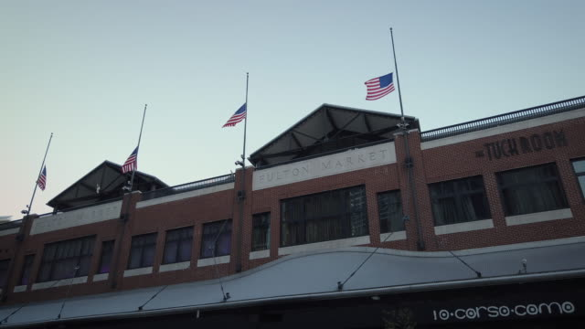 new york fulton market with us flags on halfmast building exterior during sunset filmed during coronavirus pandemic - home showcase interior stock videos & royalty-free footage