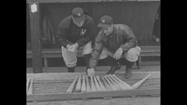 New York Giants manager Bill Terry in dugout / VS New York Yankees' Lou Gehrig chooses bat and broadly smiles during home opener at Yankee Stadium /...