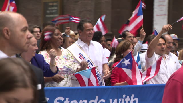 new york gov andrew cuomo marches in the puerto rican day parade waving the puerto rican flag alongside public advocate letitia james - andrew cuomo stock videos and b-roll footage