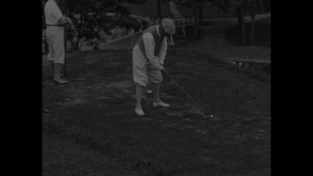 stockvideo's en b-roll-footage met cu of new york governor al smith in golf cap with son / smith tees off / another man tees off / group crosses bridge over stream / smith putts... - al smith