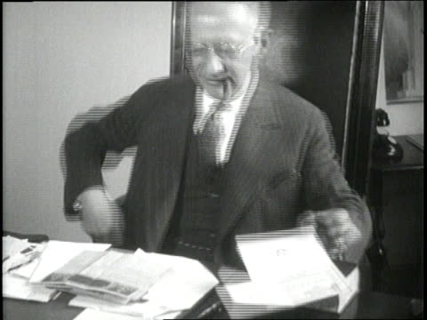 new york governor alfred e smith puts on eyeglasses lights a cigar and reads papers at his desk - sigaro video stock e b–roll